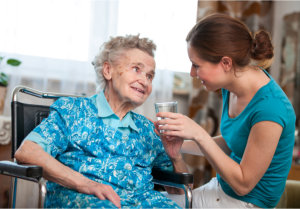 caregiver giving elderly woman water