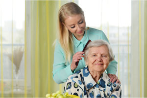 caregiver combing elderly woman's hair