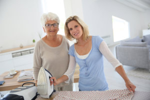 caregiver ironing elderly woman's clothes